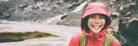 Active outdoors people lifestyle - happy hiker Asian woman laughing in the rain on mountain hike - Outdoors adventure trek activity, wearing waterproof raincoat sportswear clothes. Banner panorama. Stock Photo