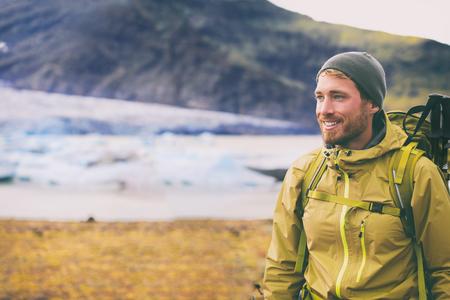 Escursione invernale sulla montagna di neve uomo felice dell'escursionista che cammina nel deserto di ghiaccio in Islanda. Viaggio avventuroso in Europa nel paesaggio naturale. Persona che indossa un cappello e una giacca per il freddo, borsa, bastoncini da trekking. Archivio Fotografico