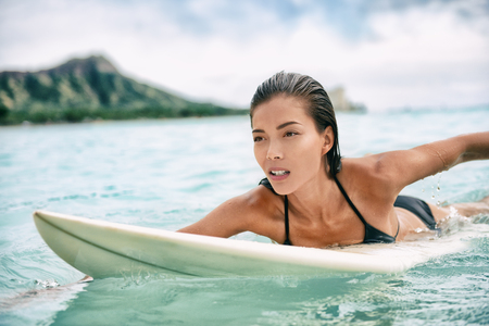 Surfing Asian woman surfer girl on surf lesson in Hawaii paddling on surfboard in ocean. Sexy sports athlete training in water. Watersport active lifestyle. Stock Photo