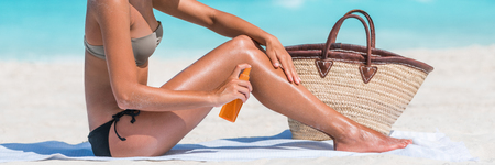 Sunscreen sun lotion woman putting sunblock cream or tan oil spray on legs during tropical summer vacation travel. Crop of lower body girl tanning on beach banner panorama.