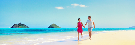 Hawaii vacation couple walking relaxing on white sand and pristine turquoise ocean water on Hawaiian beach Lanikai, Oahu island, USA. Holiday background with blue sky copy space for travel concept.