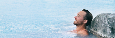 Wellness Spa man relaxing in hot springs outdoor at luxury resort spa retreat. Handsome young male model with eyes closed resting in natural water pool on travel vacation holiday. banner background. Banque d'images - 114551239