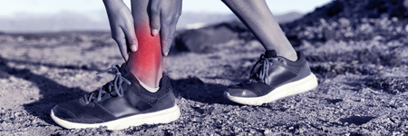 Medical health injury runner woman with hurting twisted ankle. Sports injury fitness athlete with red inflamed pain. Panorama banner. Stock Photo
