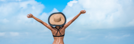Beach summer vacation woman in happy freedom concept with arms up in success. Tourist vacation girl wearing sun hat banner with copy space on blue sky.