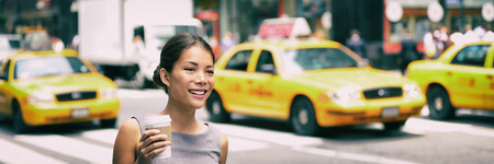 New York city commute - Asian business woman walking to work in the morning commuting drinking coffee cup on NYC street with yellow cabs in the background banner. People commuters lifestyle. Stock Photo