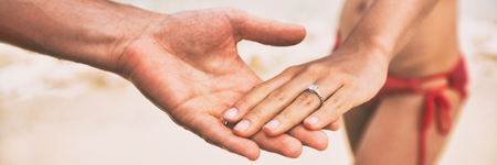 Diamond ring wedding engagement proposal hands of newlyweds on beach banner panorama. Marriage proposal with bands. Stock Photo