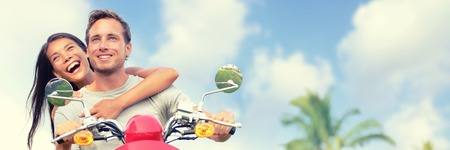 Couple tourists travel fun riding scooter for road trip summer vacation. Banner panoramic landscape header crop. Smiling young woman, man in love. Stock Photo