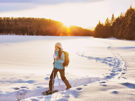 Winter sport woman hiking in snowshoes. Snowshoeing girl in the snow with shoe equipment for outdoor walking in forest trail. Quebec, Canada. Archivio Fotografico