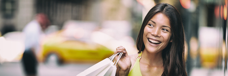 Shopping in New York City Asian woman smiling happy holding shopping bag panoramic banner background. Girl looking to the side with yellow cabs taxi cars header. Stock Photo