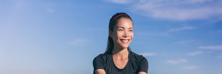 Healthy smile Asian girl portrait outside against blue sky background with copy space. Banner panorama. Chinese multiracial woman face active lifestyle happy living.