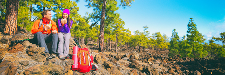 Mountain hike couple hikers eating on camping break with backpacks in autumn. Happy healthy active people on trek banner panorama.