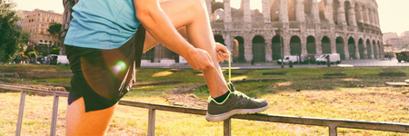 Running shoes - closeup of man tying shoe laces. male sport fitness athlete runner getting ready for jogging outdoors on Rome city street in summer. Banner panorama.