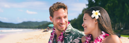 Hawaii tourists couple on beach vacation wearing lei necklace and flower for luau dance party. Tropical background banner travel lifestyle.