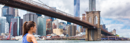 New York city woman looking at Brooklyn bridge and NYC skyscrapers view. Urban lifestyle girl walking during summer travel in USA. Asian tourist panorama skyline banner.