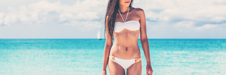 Summer bikini body weight loss woman with toned abs and slim stomach on beach background. Panorama banner of swimsuit model tanning in sun, sexy girl relaxing. Stock Photo