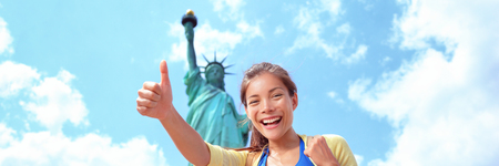 New York City tourist woman at Statue of Liberty happy doing thumbs up banner panorama. Asian girl on USA vacation travel. Young multiracial woman Asian Caucasian woman student with bag .