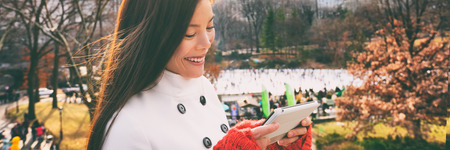 Woman walking happy in Central park, New York City in winter with Wollman skating rink using tech device smart phone tablet app for directions, tourist guide. Candid smiling -girl on Manhattan, USA. Stock Photo