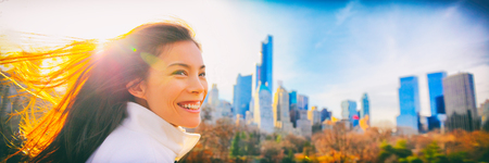 Woman walking smiling in Central park, New York City in winter background banner of NYC cityscape skyscrapers buildings skyline, Sun shine healthy Asian girl. Candid portrait on Manhattan, USA.