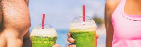 Green smoothie fit fitness healthy people drinking juice at exercise workout. Closeup of couple hands holding detox drink outdoors. Banner panorama. Stock Photo