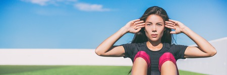 Sit ups - fitness woman exercising sit up outside in grass in summer. Fit athlete crossfit training in summer. Asian sports model in her 20s banner panorama with copy space. Stock Photo