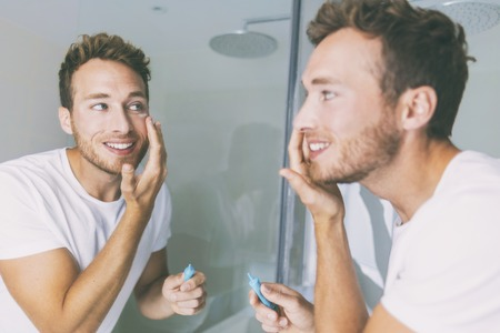 Man putting skincare facial treatment cream on face. Anti-aging skin care product. Male beauty morning routine at home lifestyle. Guy looking in bathroom mirror applying moisturizer under eyes. Stock Photo