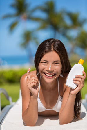 Sunscreen woman applying lotion putting cream on nose. Beautiful smiling happy asian woman with suntan cream bottle lying down during summer travel vacation. Multiracial female model