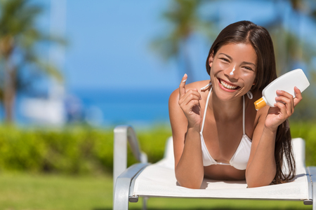 Suntan lotion woman applying sunscreen solar cream. Beautiful happy cute woman asian applying suntan cream from a plastic container to her nose with ocean in background. 版權商用圖片