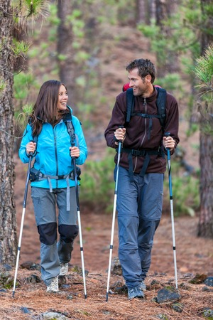 Happy couple hikers talking together on outdoor nature walk. Young multiracial people hiking outdoors in forest. Smiling Asian woman and Caucasian man. Stok Fotoğraf