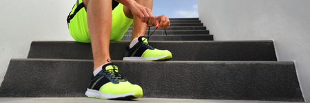 Runner man tying running shoes laces getting ready to run banner on city stairs. Healthy active lifestyle athlete jogging header panoramic crop. Stock Photo
