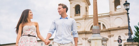 Romantic couple walking on Europe city travel holiday. Interracial young people holding hands on summer romance vacation panorama banner. Rome, Italy, European cruise destination. Banco de Imagens