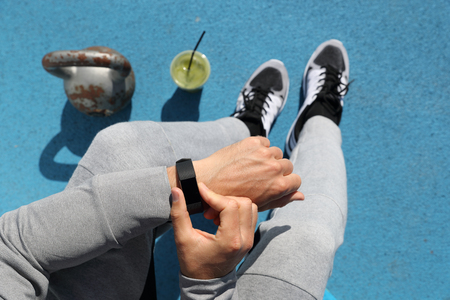 Gym man touching smartwatch screen during workout strength training. Top view from above: kettlebell weights, green smoothie, body and legs. POV of athlete sitting resting. Healthy fitness lifestyle. Stock Photo