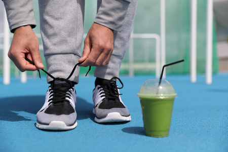 Gym fitness man getting ready tying running shoes with green smoothie detox beverage. Closeup of running trainers with plastic cup of breakfast vegetable juice. Sport active lifestyle. Stock Photo