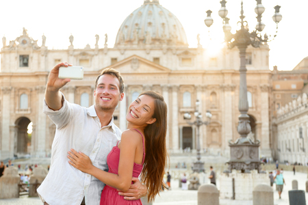 Europe luxuy travel vacation tourists in Rome, Italy. Honeymoon vacation couple taking selfie photo with phone at Vatican city St Peters Basilica church at sunset. Summer holiday cruise destination.