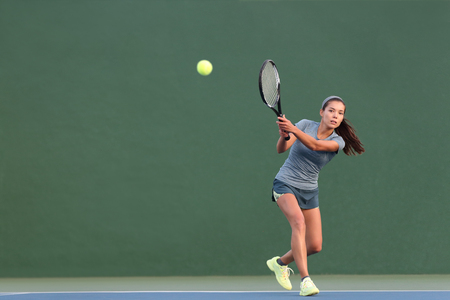 Tennis playing woman hitting ball on green hard court. Asian athlete girl returning serve with racket wearing skort and shoes. Stock fotó