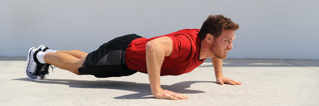 Pushup fitness man banner doing push-ups workout bodyweight exercise on gym floor. Athlete working out chest muscles strength training outdoors panoramic crop. Stock Photo