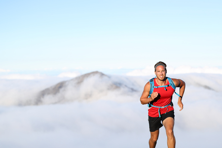 Trail runner man athlete running in mountains outdoor nature with mountain peak in clouds in background.