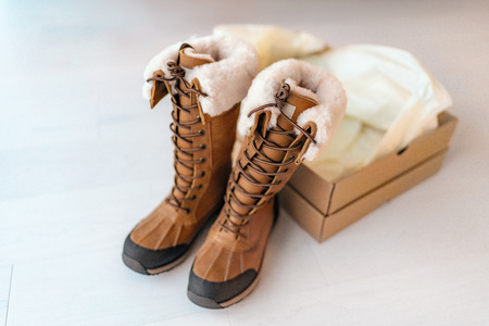 New winter hiking boots with open shoebox buying new shoes online shopping from home. Tall waterproof leather and sheepskin luxury footwear for winter. Stock Photo