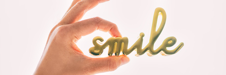 Smile decoration expression object for home positivity wellness. Woman hand holding sculpture written SMILE in gold brass metal. Banner panorama. Motivational quote.