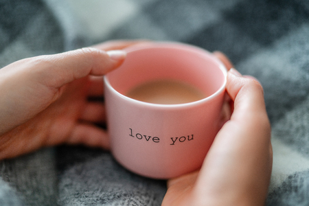 Winter warm coffee cup woman relaxing at home cozy with wool blanket - morning breakfast girl drinking with the words LOVE YOU written on pink mug for valentines day. Romantic quote. Stock Photo