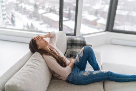 Dolor de cabeza y depresión - ansiedad de la tristeza invernal mujer que se siente enferma sosteniendo la cabeza y el estómago con dolor - dolor del período menstrual o cansado.