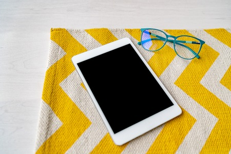 Tablet on dining table with reading glasses - blue light protection from looking at bright screens from tech devices. Technology lifestyle. Stock Photo