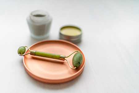 Luxury skincare korean beauty products - creams, balm and mud mask jars with jade stone face roll massager - Facial roller massaging therapy. 免版税图像 - 115006628