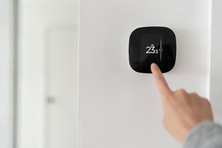 Smart home termostato digitale touch screen donna che tocca il touchscreen per regolare la temperatura del riscaldamento nella parete del soggiorno.