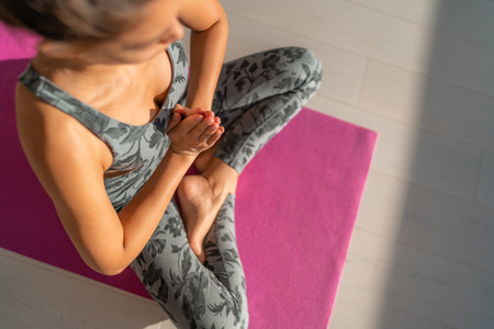 Yoga meditation woman praying with hands in prayer on heart - . Meditating on pink exercise mat at yoga retreat- Wellness and wellbeing concept.