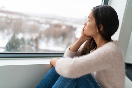 Winter seasonal affective disored SAD depression mood alone Asian girl feeling lonely - stress, anxiety, melancholy emotions. Sadness at home. Stockfoto