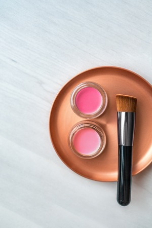 Makeup brush with blush pink and rouge color cream jars palette on stainless steel mixing plate - Make-up professional tool for artist. Top view background.
