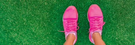 Feet selfie of pink fashion running shoes POV standing on grass of city park. Girl ready to go jogging outside walking on copy space banner background. Stock Photo