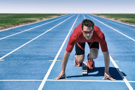 Atleta velocista listo para comenzar a correr la carrera esperando en la línea en los bloques de salida en pistas azules en el estadio al aire libre. Enfoque y motivación concepto de deporte y fitness.