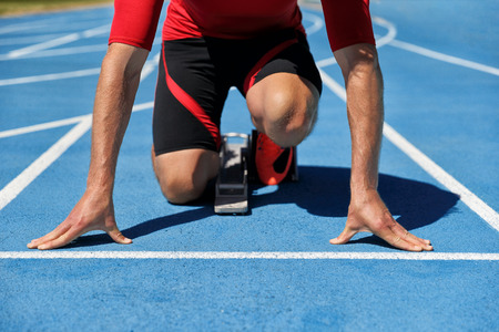 Runner athlete starting running at start of run track on blue running tracks at outdoor athletics and fiel stadium. Sport and fitness man lower body, legs and running shoes going sprinting. Stock Photo