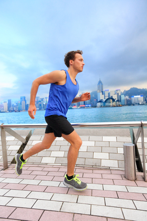 Active sport runner man jogging in Hong Kong harbour city street living a healthy urban lifestyle training morning workout. Caucasian expat male athlete working out cardio.